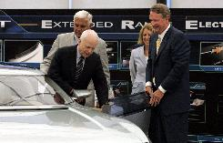 Republican presidential candidate Senator John McCain (R-AZ) steps into a Chevy Volt Electric Concept vehicle as General Motors Chairman and CEO Rick Wagoner, right, Vice Chairman Bob Lutz, left, and Vice President of Environment and Energy Beth Lowery watch at the GM Technical Center in Warren, Michigan.