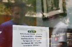 A restaurant window menu displays the calorie count for each food item in New York. Several fast food chains say they have finally begun obeying a new city rule requiring some restaurants to post calorie counts on the menu.