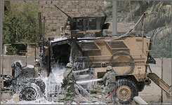 U.S. soldiers try to extinguish an American armoured vehicle at Al Canal street, near Sadr city, Baghdad.  Through June 2008, there were only 93 attacks on about 6,100 logistics convoys carrying supplies ranging from building materials for schools, hospitals and public utilities to weapons for local police.