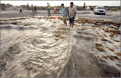 Dora and Ernesto Guevara watch as water surges from Hurricane Dolly wash up on Whitecap Drive in Padre Island, Corpus Christi, Texas, on Tuesday.