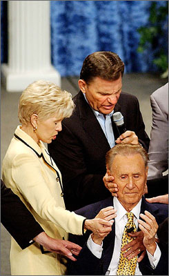 Gloria Copeland and Kenneth Copeland lay hands on Oral Roberts during the International Charismatic Bible Ministries conference in Tulsa, Okla.