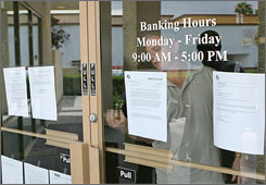 A man locks the door to a 1st National Bank of Nevada branch after handing contact information to journalists Saturday in Las Vegas.