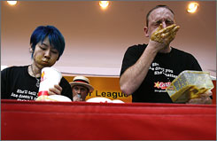 Takeru Kobayashi, left, and rival Joey Chestnut are seen during a satay eating contest in Singapore.