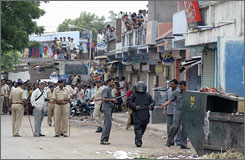 Policemen stand guard as bomb squad personnel prepare to defuse a live bomb in Ahmadabad, India, on Sunday.