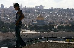 The Dome of the Rock Mosque is seen in Jerusalem's Old City, as a Palestinian boy walks on a wall on the Mount of Olives, Monday, July 28, 2008. Jerusalem remains one of the toughest sticking points in the peace process.