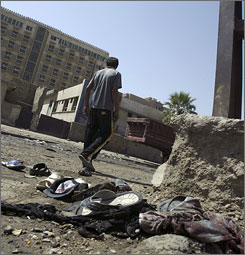 Police say 57 people died in suicide bombs in Iraq on Monday, police say. Here, a man walks past the scene of one of those bombings in northern Baghdad.