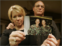 Peggy and Jeff Hubbard hold a photograph of their sons Jason, left, and Nathan, taken in Clovis, Calif. Army Spc. Nathan Hubbard was killed in a helicopter crash in Iraq on Aug. 22, 2007. Nathan Hubbard had joined the Army after their brother Marine Lance Cpl. Jared Hubbard was killed in Iraq in 2004.