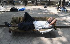 The number of homeless people in America is on the decline, according to a new report by the Department of Housing and Urban Development. Here, Vernon Robinson stretches out on a bench in June in a Baltimore church park that is open to the homeless.