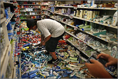 Corey Dixon, 14, sifts through deodorant to purchase from K-Mart during the aftermath of a 5.4-magnitude earthquake near Diamond Bar, Calif., on Tuesday. Nearly 30 aftershocks quickly followed, the largest estimated at 3.8. The quake was centered 29 miles southeast of downtown Los Angeles near Chino Hills, a San Bernardino County city.