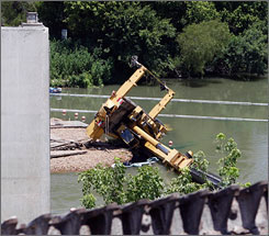 Workers were attempting to remove parts of the old bridge, in the foreground, when a mobile crane fell and killed one worker.