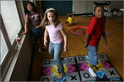 Kaitline Warnke, 8, and Elijah Villarreal, 10, play Dance Revolution Extreme at the Corpus Christi YWCA.