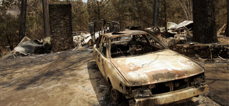 The burnt remains of a home and car stand in Mariposa, Calif., near Yosemite National Park.