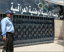 A security member stands guard at the entrance to the National Olympic Council of Iraq building in Baghdad Saturday.