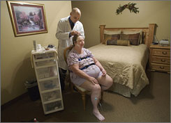 Sleep technologist Christopher Kinsey applies electrodes on Rose Ann Bestlin during a sleep study at Valley Oximetry Sleep Disorders Center in Mesa, Ariz. Bestlin had been diagnosed with sleep apnea.
