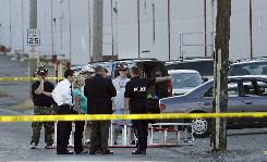 Investigators and firefighters stand outside of a warehouse in the Bristol Borough of Philadelphia on Friday. Two people are dead after a shooting outside the suburban Philadelphia book warehouse, and a man described as a disgruntled former employee is in custody.