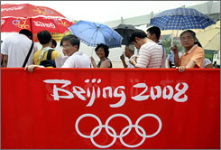 In this July 25 file photo, people queue up for the last batch of Olympic tickets outside of Shanghai Stadium in Shanghai. China's hopes that the Olympics would be a pivotal moment in national glory and global acceptance have been battered, as unforeseen events collided with its grand ambitions.