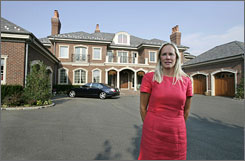 Real estate agent Margaret Trautmann is trying to sell the Muttontown, N.Y. home behind her in this photo. It may have taken longer and it may not be as acute, but there are early hints that the economic slump is crimping the lifestyles of the wealthy.