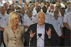 Republican presidential candidate, Sen. John McCain, R-Ariz., right, and his wife Cindy speak to reporters, with factory workers in the background, after a tour of the National Label Company Monday in Lafayette Hill, Pa.