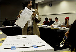 Jenean Harper (center), the training coordinator at the Cuyahoga County Board of Elections, plays the role of voter in a mock voting scenario as she leads a training session for poll workers at the East Cleveland Public Library. Ohio has switched this year to optical scan paper ballots instead of electronic voting machines.