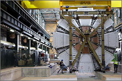 The last element, weighing 100 tons, of the ATLAS experiment is lowered into the cave at the European Organization for Nuclear Research near Geneva, Switzerland, in February. ATLAS is part of five experiments which will study what happens when beams of particles collide in the 17-mile underground ring. ATLAS is one of the largest collaborative efforts ever attempted in the physical sciences.