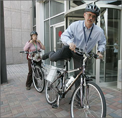 Emory University employees David Knight and Casey Brinsfield use the school's bank of loaner bicycles to get to a meeting on the Atlanta campus. Emory is selling discounted bikes to students and faculty, adding bike lanes to campus roads and stocking bikes that can be borrowed free of charge.