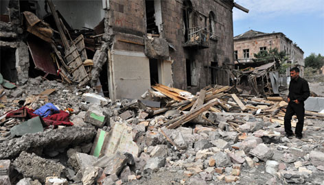 A Georgian man stands among ruins in front of his damaged home in Gori on Monday. The conflict has already forced about 40,000 people from their homes, an International Committee of the Red Cross spokeswoman said.