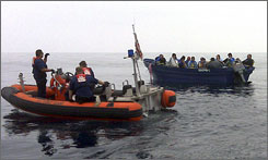 U.S. Coast Guard officers move in on a boat packed with suspected illegal immigrants last month.