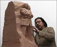 "Sculptor Lei Yixin of China looks at a scale model of the ""Stone of Hope,"" a piece he created as the centerpiece for the Rev. Martin Luther King, Jr. memorial."