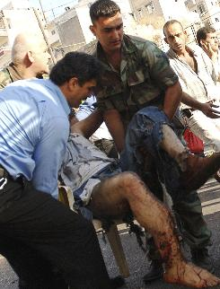 A Lebanese soldier and civilian man, help an injured man at the scene of a bomb explosion, in the northern city of Tripoli, Lebanon.