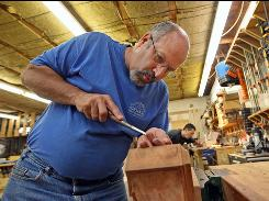 Craftsman Jeff Dixon works on July 14 at Kinloch Woodworking, a manufacturer of high-end furniture in Unionville, Pa.