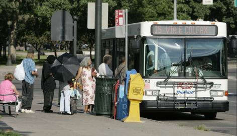 Passengers board a RTD bus in downtown Denver in July. Americans have decreased miles driven over last year for the eighth consecutive month in part by turning to public transportation. But as gas prices fall, they may begin to abandon these new habits.