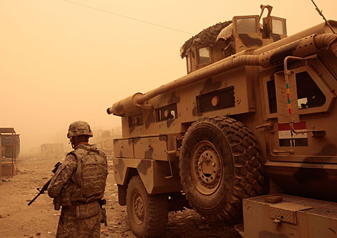 A U.S. Army soldier of the 4th Infantry Division stands next to an Iraqi Army armored vehicle in a deserted market area that recently saw heavy fighting in Sadr City. One-third of soldiers exposed to heavy combat show signs of mental problems, according to the U.S. Army Surgeon General.