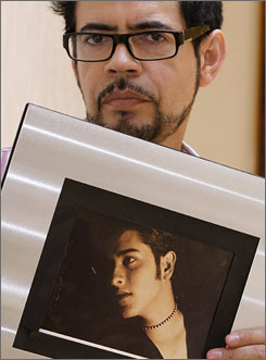 Jorge Saavedra, a Mexican federal official, holds a photo of his partner Fernando, in Mexico City.