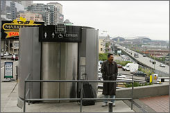 A man waits for his turn to use an automated public toilet, near Seattle's famous Pike Place Market. The five high-tech self-cleaning toilets cost Seattle $5 million but sold online for just $12,549.