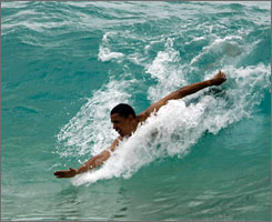 Democratic presidential contender Barack Obama, the senator from Illinois, body surfs in Honolulu on Thursday during his last full day of vacation in his native Hawaii.
