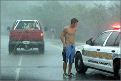 A Monroe County Sheriff stops Kyle Holloran, 20, from being towed behind a truck while riding a board in Islamorada, Fla., during Tropical Storm Fay on Monday.