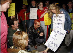 Members of the Communications Workers of America listen to union members talk on a cellphone during an informational picket outside a Qwest Communications International Inc. facility near Denver on Sunday, Aug. 17, 2008.