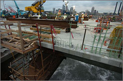 Crews work on the new I-35W bridge over the Mississippi River in Minneapolis. The old bridge's collapse last year helped boost spending on such public projects.