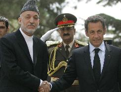 Afghan President Hamid Karzai, left, shakes hand with French President Nicolas Sarkozy at president palace in Kabul, Afghanistan. Sarkozy visited a military chapel in Kabul where the bodies of 10 French soldiers killed in battle lay before they were to be flown home.