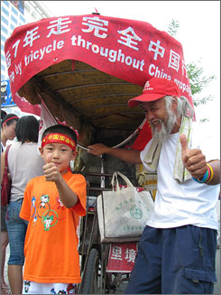 Chen Guanming, right, shows the tricycle he rode across the country to a young Olympics fan in Beijing.