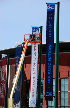 Real Americans will be featured during the Democratic National Convention, slated to start Monday in Denver. Here, workers hang banners outside of the Pepsi Center in Denver in preparation.