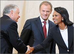 Condoleeza Rice shakes Polish President Lech Kaczynski's hand as Poland's Donald Tusk watches.