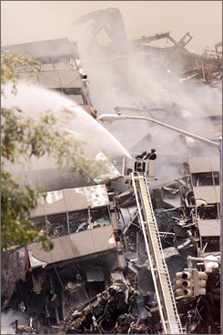 A new report refutes speculation by conspiracy theorists that 7 World Trade Center, seen here on Sept. 12, 2001, as firefighters work at the wreckage site, was destroyed by explosives.
