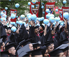Graduates from Harvard's Kennedy School of Government celebrate by holding inflatable globes in the air during Harvard University commencement exercises, Thursday, June 5, 2008, in Cambridge, Mass.