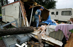 George Sweat, 46, searches for his valuables after a large pine tree fell on his home, as girlfriend Peggy Mash, 53, played on her couch with her two cats, at right, during Tropical Storm Fay Aug. 22 in Hawthorne, Fla.