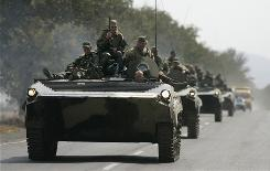 Russian soldiers ride near the village of Khurvaleti on Friday, moving north in the direction of South Ossetia. A top Russian general said it could be 10 days before the bulk of the troops are gone.