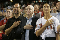 John McCain is flanked by Olympic gold medalist Misty May-Treanor and Diamondbacks CEO Jeff Moorad at an Arizona Diamondbacks baseball game Sunday in Phoenix.