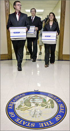 Arkansas Family Council Action Committee President Jerry Cox, center, and two aids carry boxes of petitions to ban adoption for unmarried couples at the state Capitol in Little Rock Thursday.