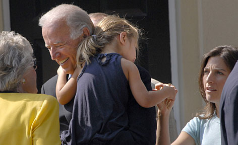 Democratic vice presidential running mate Joe Biden carries granddaughter Natalie Biden out of St. Joseph Catholic church in Greenville, Del., on Aug. 24. Hallie Biden, right, hands her daughter a necklace as other parishioners greet the senator.