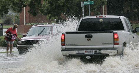 Traffic passes through street flooding after torrential rains spawned by Fay, downgraded to a topical depression, deluged Montgomery, Ala., Monday.